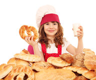 Little girl cook with pretzel and glass of milk Stock Images