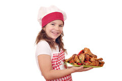 Little girl cook with roasted chicken drumsticks Stock Photos