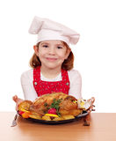 Little girl cook with roasted chicken on table Royalty Free Stock Photos