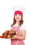 Little girl cook with roasted chicken wings Royalty Free Stock Images