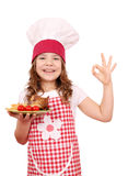 Little girl cook with roasted chicken wings and ok hand si Stock Image