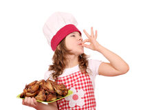 Little girl cook with roasted chicken wings Stock Photo