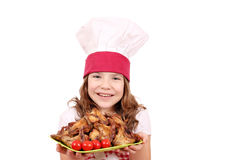 Little girl cook with roasted chicken wings on plate Stock Photo