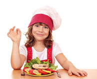 Little girl cook with salmon Stock Images
