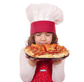 Little girl smells pizza Stock Photos