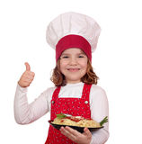Little girl cook with spaghetti and thumb up Stock Images