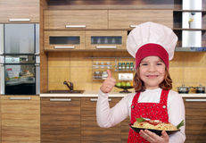 Little girl cook with spaghetti and thumb up in kitchen Stock Photos