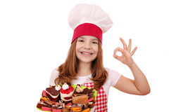 Little girl cook with sweet cakes andok hand sign Royalty Free Stock Photo