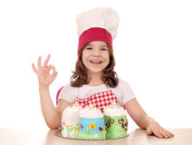 Little girl cook with sweet cakes and ok hand sign Royalty Free Stock Image