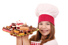 Little girl cook with sweet cakes on plate Royalty Free Stock Image