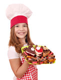 Little girl cook with sweet cakes on plate Stock Photos