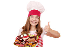 Little girl cook with sweet cakes and thumb up Royalty Free Stock Photo