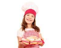 little girl cook with sweet donuts on plate Stock Images