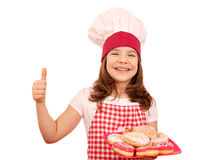 little girl cook with sweet donuts and thumb up Stock Photo