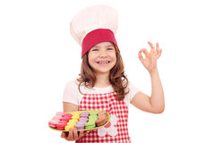 Little girl cook with sweet macarons and ok hand sign Royalty Free Stock Photos