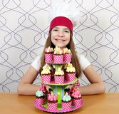 Little girl cook with sweet muffins on table Stock Images