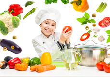 Little girl-cook by table with flying vegetables Stock Photography