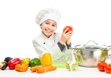Little girl-cook by table with vegetables Royalty Free Stock Photography