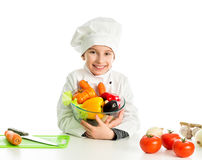 Little girl-cook by table with vegetables Stock Image