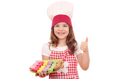 Little girl cook with thumb up and macaroons Royalty Free Stock Image