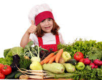Little girl cook with thumb up and vegetables Stock Image
