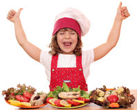 Little girl cook with thumbs up and seafood Royalty Free Stock Images