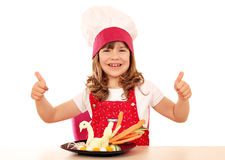 Little girl cook with thumbs up and white swan decorated s Stock Photos