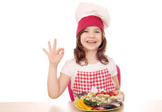 Little girl cook with trout and ok hand sign Royalty Free Stock Images