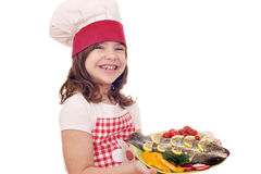 Little girl cook with trout on plate Royalty Free Stock Images