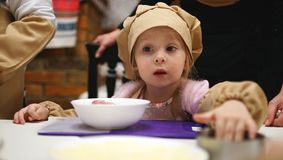 Little girl in a cooking caps playing in cafe. Concept of cooking classes. Little girl in a cooking caps and aprons with interested look playing in cafe. Concept stock images