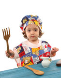 Little girl cooking dressed as a chef. Cute toddler cooking dressed as a chef. More pictures of this baby at my gallery royalty free stock image