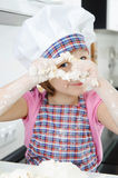 Little girl cooking in kitchen Stock Images