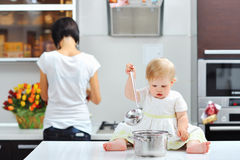 Little girl cooking on a kitchen with mother in the background Royalty Free Stock Photography