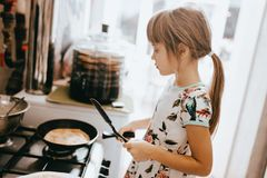 Little girl is cooking pancakes for the breakfast in the little cozy kitchen stock image