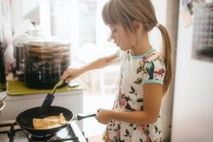 Little girl is cooking pancakes for the breakfast in the little cozy kitchen royalty free stock photo