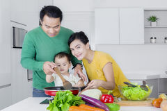 Little girl cooking with parents in kitchen. Little girl cooking vegetables with her parents while standing in the kitchen Royalty Free Stock Photos