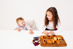 Little girl cooking pastry with her brother Stock Images