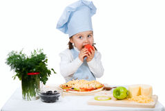Little girl  cooking pizza and eating tomato Royalty Free Stock Photos