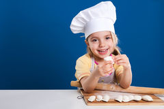 The little girl is cooking and preparing food on blue background Royalty Free Stock Image