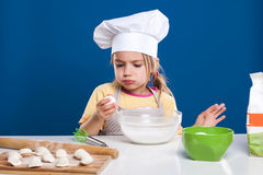 The little girl is cooking and preparing food on blue background Royalty Free Stock Photography