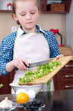 Little girl  is cooking salad from fresh ingredients Stock Photography
