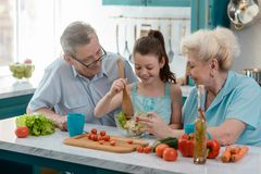 Little girl cooking salad stock images