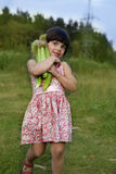 Little girl with corn Stock Images
