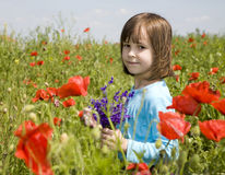 Little girl and corn poppy Stock Images