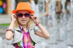 Little girl corrects sunglasses Stock Photos
