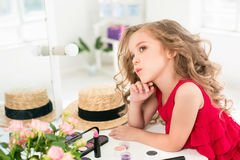 A little girl with cosmetics. She is in mother`s bedroom, sitting near the mirror. A little girl with red dress and cosmetics. She is in mother`s bedroom Stock Photos