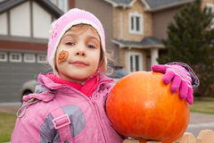 Little girl costs in court yard with pumpkin Stock Images