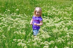 Little girl costs in a grass outdoors Stock Photos