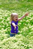 Little girl costs in a grass outdoors Stock Photo