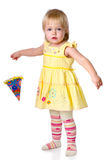 The little girl costs with a party hat in a hand Royalty Free Stock Photos